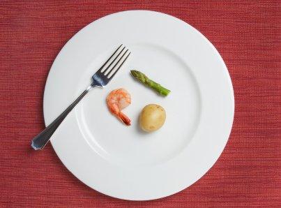 tiny meal consisting of one shrimp, a tiny potato, and a single short asparagus stalk